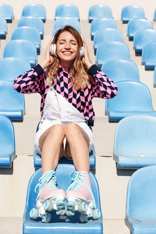 有减速火箭溜冰鞋坐的愉快的女孩 免版税库存照片