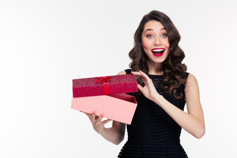 有减速火箭的发型开头礼物的激动的快乐的可爱的少妇 图库摄影