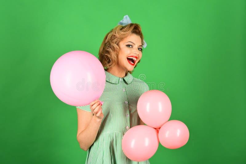有减速火箭的构成举行气球的性感的白肤金发的女孩 图库摄影