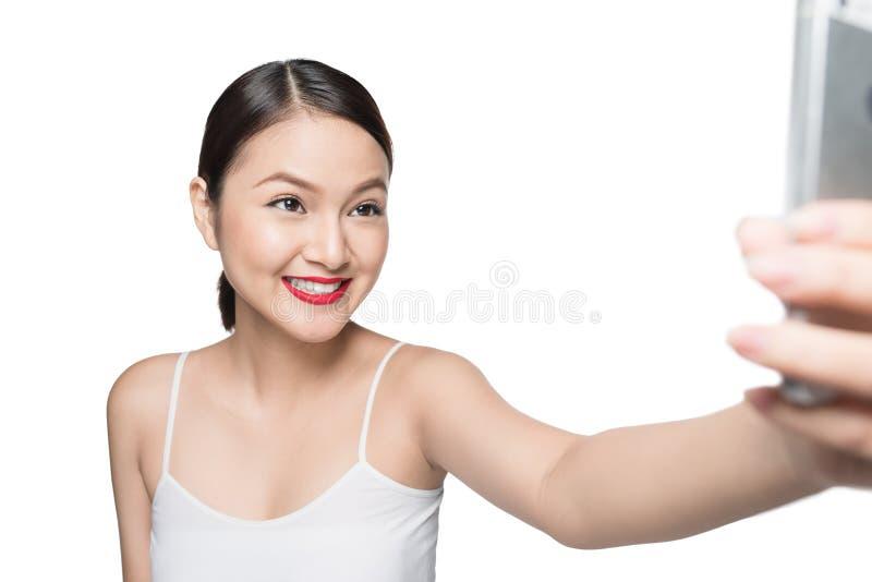 有减速火箭的构成的美丽的亚裔妇女与采取sel的红色嘴唇 免版税库存图片