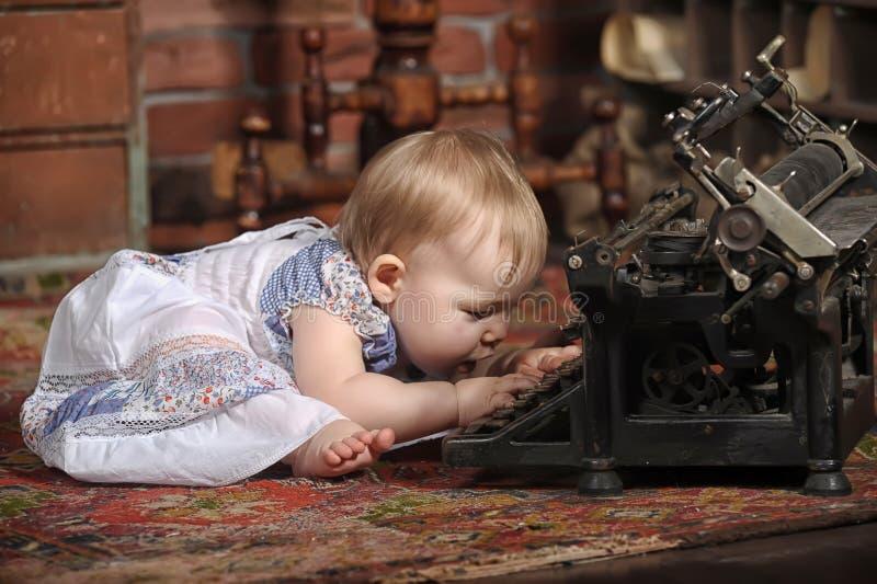 有减速火箭的样式打字机的逗人喜爱的矮小的婴孩 库存照片