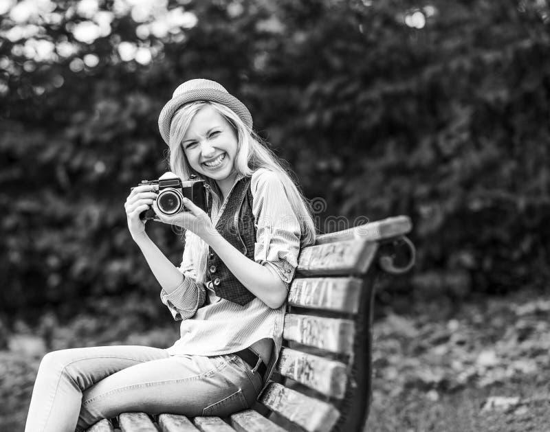 有减速火箭的照片照相机的行家女孩坐长凳  免版税库存照片