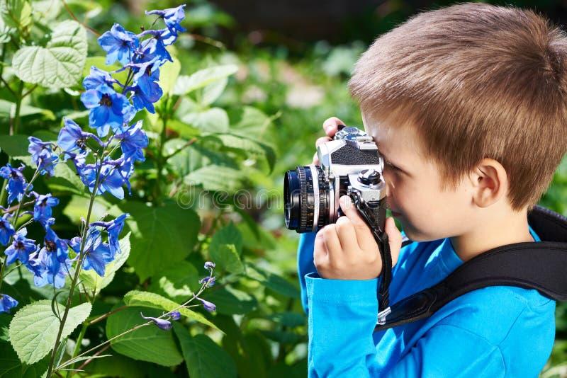 有减速火箭的照相机射击花的小男孩 库存照片