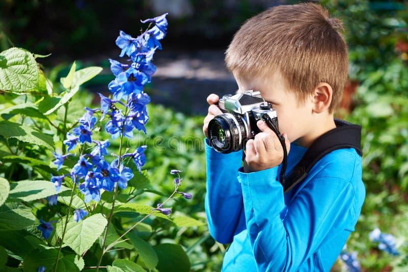 有减速火箭的照相机射击花的小男孩 图库摄影