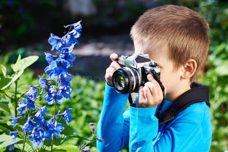 有减速火箭的照相机射击花的小男孩 免版税库存图片