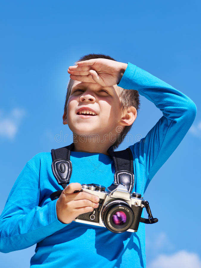 有减速火箭的照相机的小男孩在天空调查距离 免版税图库摄影