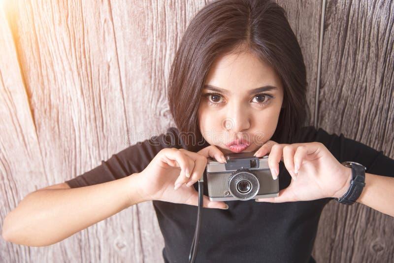 有减速火箭的照相机的逗人喜爱的年轻亚裔妇女与光 启远地行家 免版税库存图片