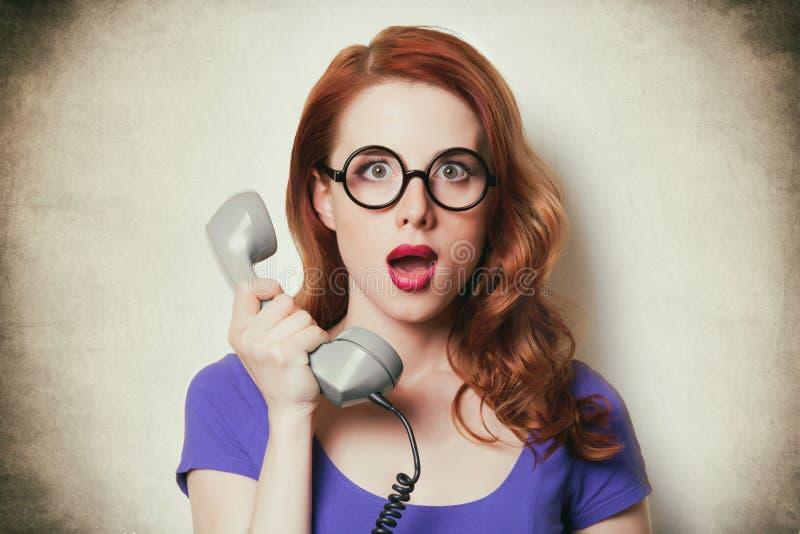 有减速火箭的电话的美丽的惊奇的少妇 免版税库存图片
