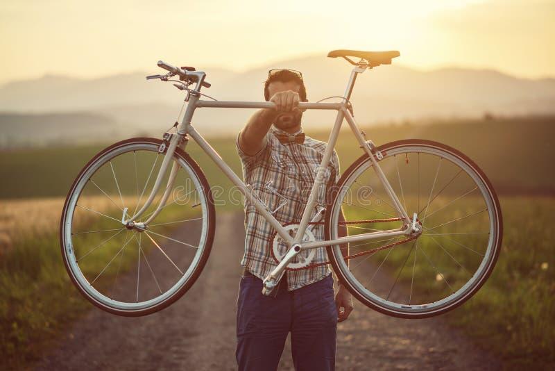 有减速火箭的自行车的年轻人在路的日落,在减速火箭的样式的时尚摄影与自行车 免版税图库摄影