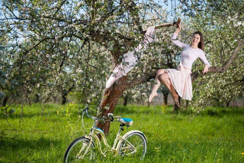 有减速火箭的自行车的美丽的女性骑自行车者在春天庭院 免版税图库摄影