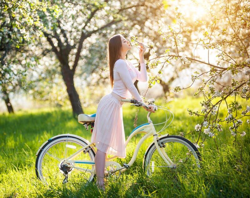 有减速火箭的自行车的美丽的女性骑自行车者在春天庭院 免版税库存图片