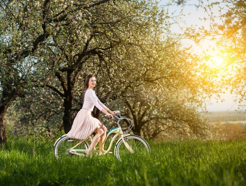 有减速火箭的自行车的美丽的女性骑自行车者在春天庭院 免版税库存照片