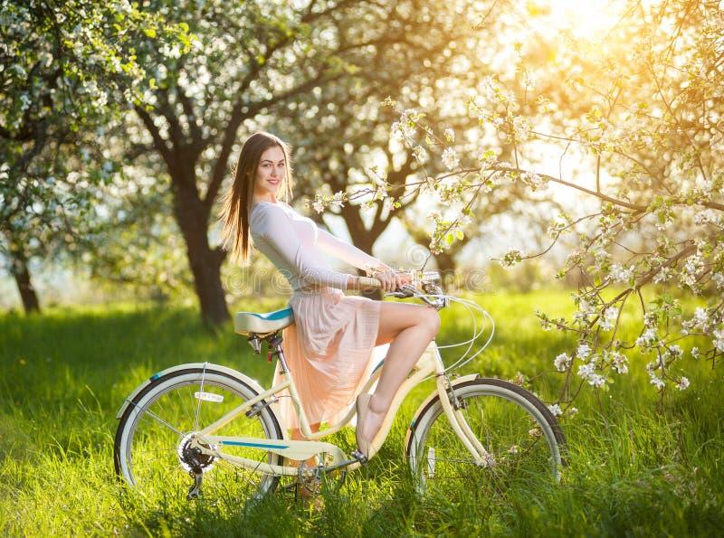 有减速火箭的自行车的美丽的女性骑自行车者在春天庭院 库存图片