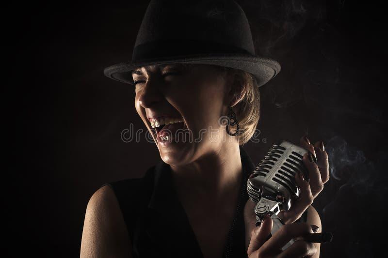 有减速火箭的话筒的微笑的爵士乐歌手 免版税库存照片