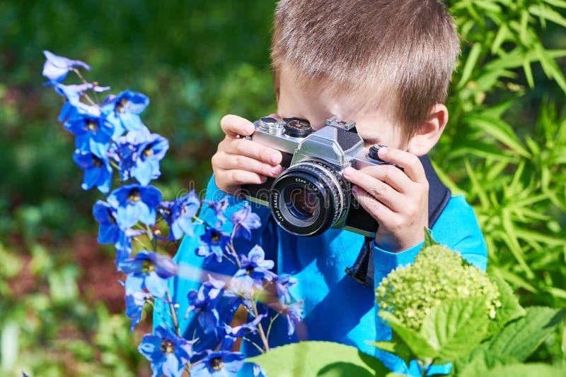 有减速火箭的SLR照相机射击宏指令的小男孩开花 免版税图库摄影