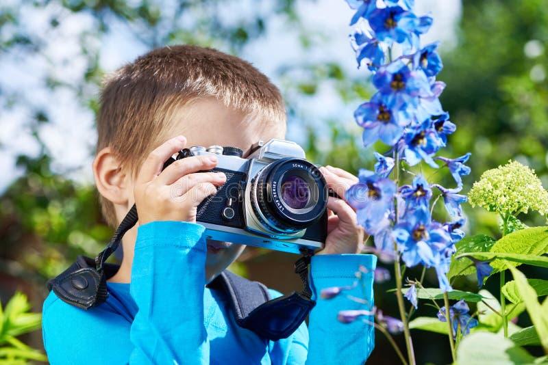 有减速火箭的SLR照相机射击宏指令的小男孩开花 免版税库存照片