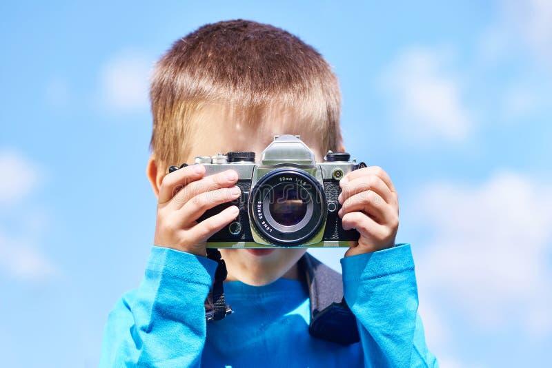 有减速火箭的SLR照相机的小男孩在蓝天 免版税库存照片