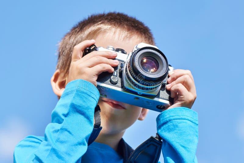 有减速火箭的SLR照相机的小男孩在蓝天 图库摄影