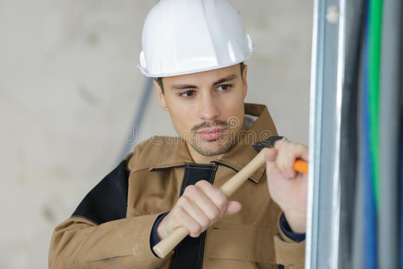 有凿子和锤子的年轻泥工恢复大厦 免版税图库摄影
