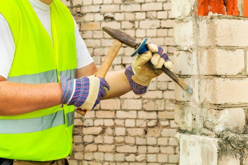 有凿子和锤子的建筑工人在砖墙附近 免版税库存照片
