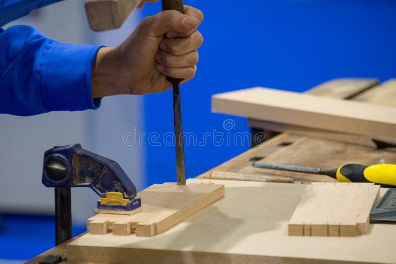 有凿子和锤子的木匠在车间 库存图片