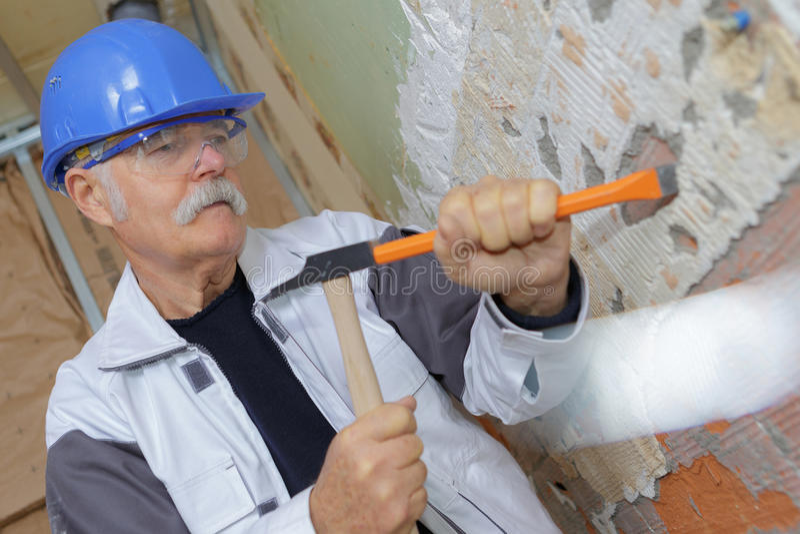 有凿子和锤子的资深建筑工人 库存图片