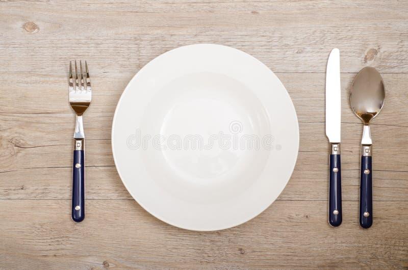 有刀子、叉子和匙子的盖子在一张餐桌上 免版税库存图片