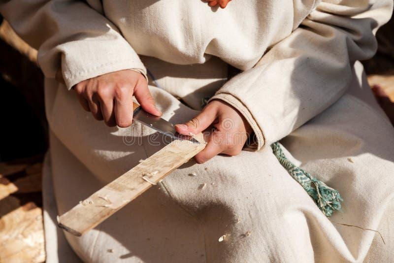 有刀子工作的手与木头,选择聚焦 免版税库存照片