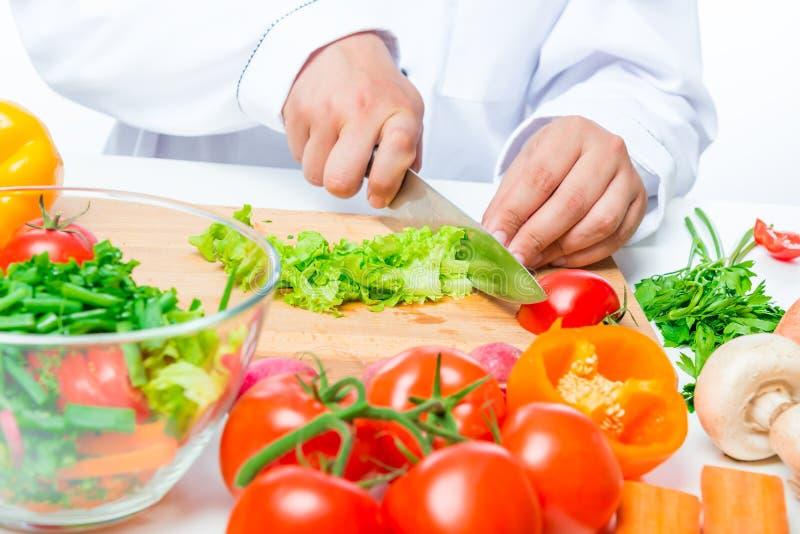 有刀子的切好的莴苣和厨师手 免版税库存照片