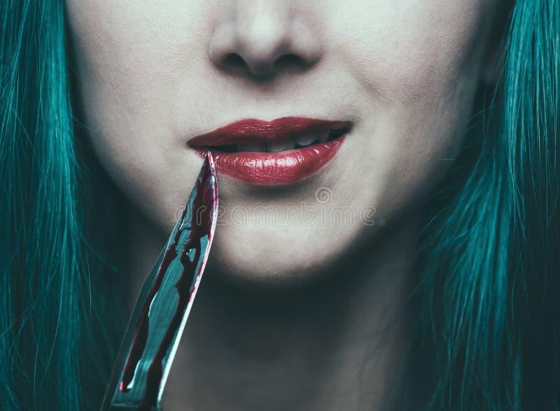 有刀子的危险妇女在血液 免版税库存照片