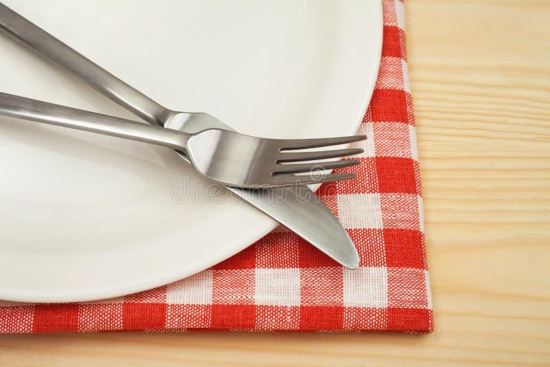 有刀子的空的在方格的餐巾的板材和叉子 库存图片