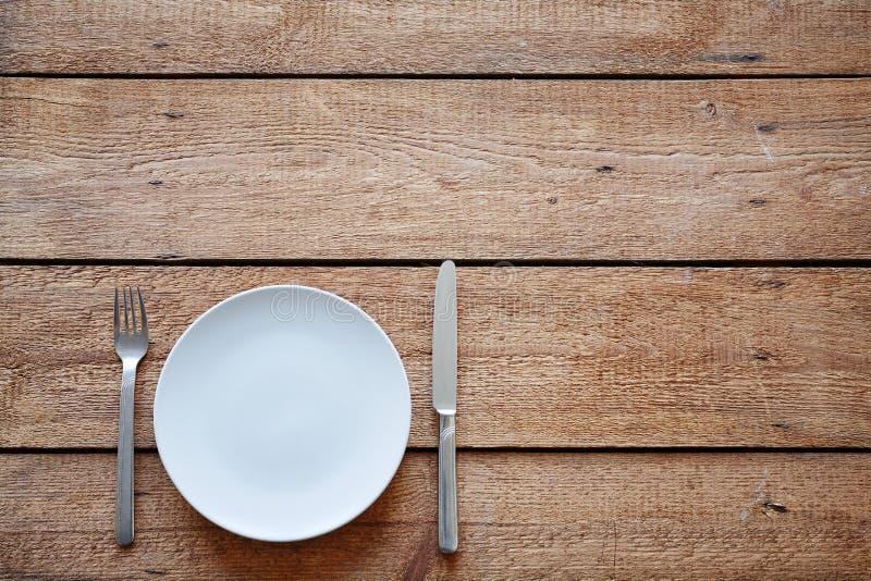 有刀子的空的在空的桌上的板材和叉子 免版税库存图片