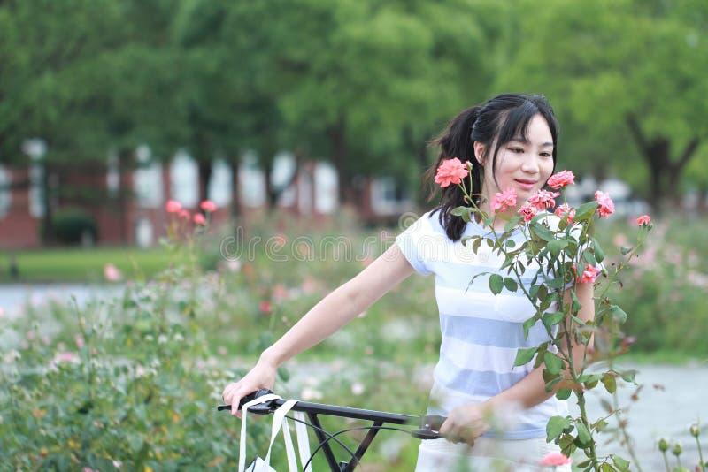 有分享的自行车亚裔中国年轻美丽,优美加工好的妇女 秀丽、时尚和生活方式 库存照片