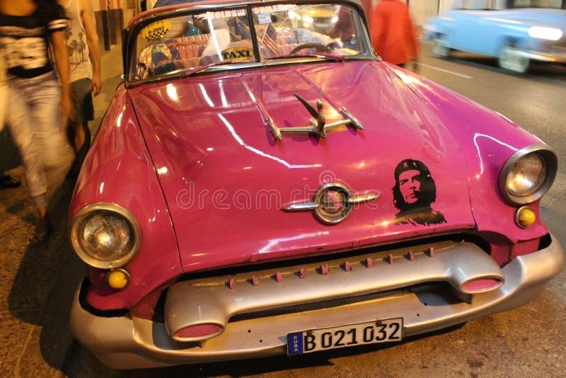 有切・格瓦拉的图片的经典美国汽车在哈瓦那,古巴街道上的  免版税库存图片