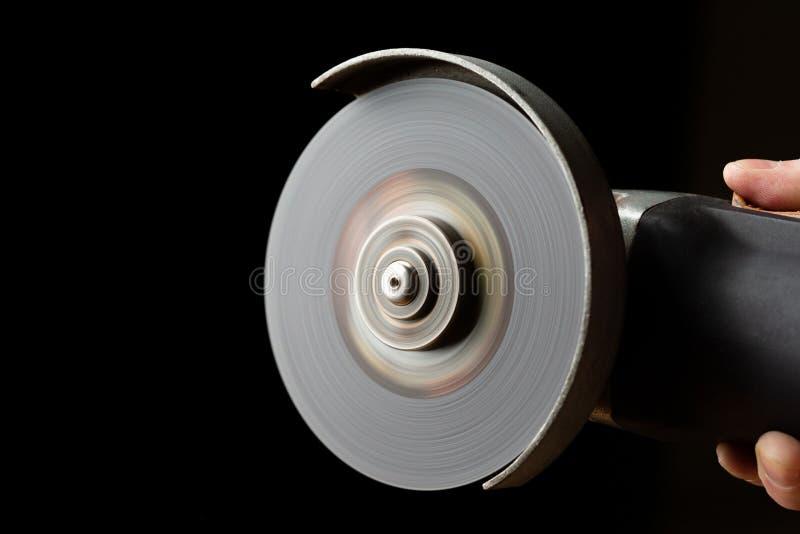 有切口轮子的手工磨床在工作的手上 免版税库存照片