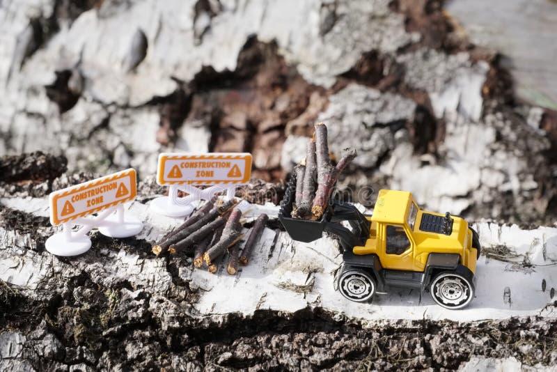 有切好的木日志和建筑的黄色玩具挖掘者签署微型看法场面 免版税库存照片