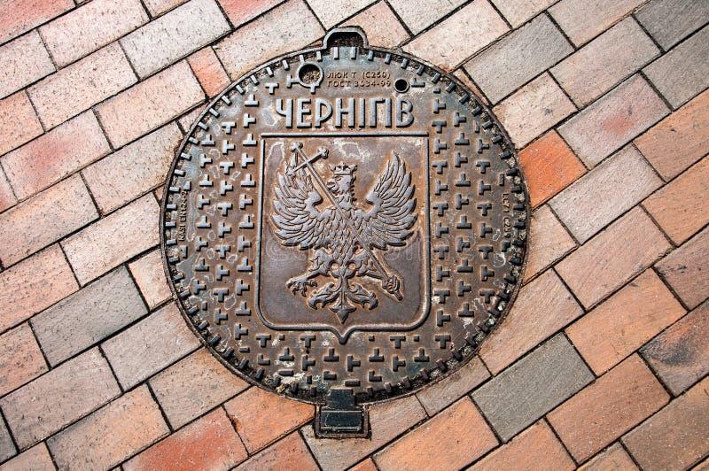 有切尔尼戈夫徽章的下水道舱口盖和城市名字 库存照片