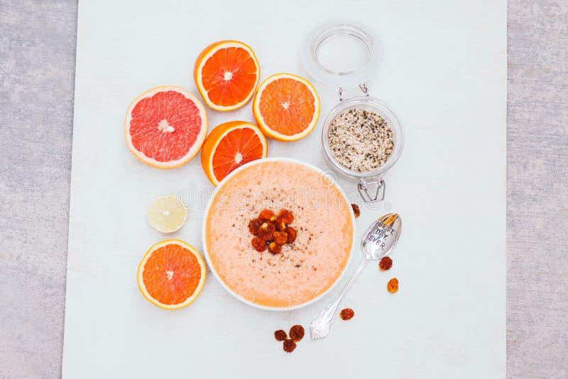 有切片的或桔子、石灰或者葡萄柚,该处绞行的人,匙子圆滑的人碗 干金黄莓果 在白色背景的隔离 ?? 免版税库存照片