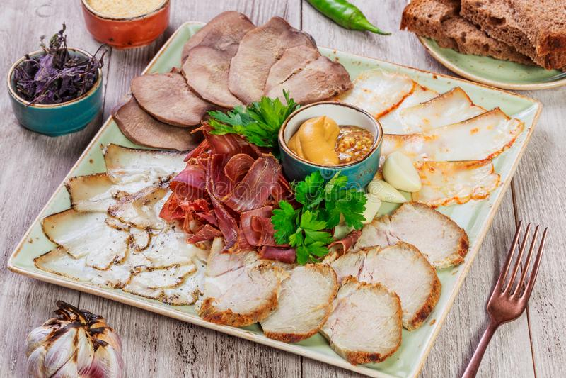 有切片的火腿,猪肉,牛舌肉,牛肉干,芥末肉盛肉盘 免版税库存照片