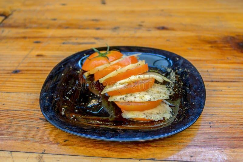 有切片的被切的蕃茄板材乳酪、香料和橄榄油 库存照片