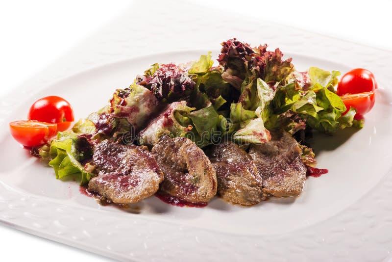 有切的火腿、香肠、橄榄、牛舌肉、草本和肉可口片断的肉板材用萝卜在白色板材 免版税库存图片
