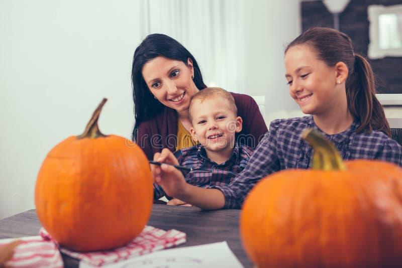 有创造大橙色南瓜的女儿和儿子的母亲 免版税库存照片