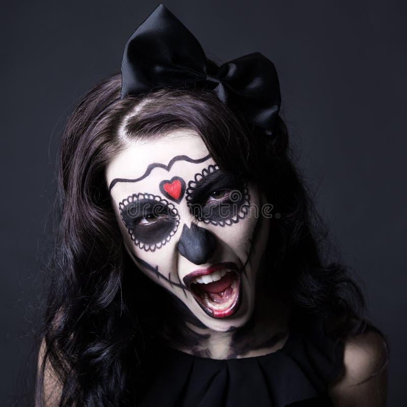 有创造性的万圣夜头骨的妇女做尖叫在黑色 免版税库存照片