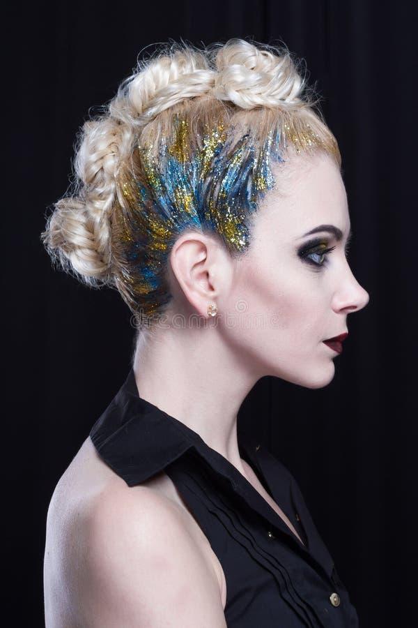 有创造性的发型的年轻可爱的白肤金发的妇女 侧视图 免版税库存照片