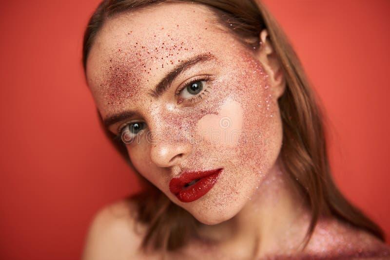 有创造性的年轻白种人女孩在面孔组成和心形的图片 免版税库存图片