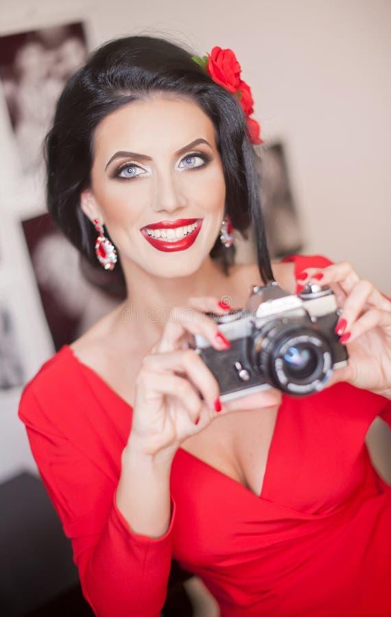 有创造性的构成和拍与照相机的发型的美丽的少妇照片 时兴的可爱的浅黑肤色的男人 免版税库存照片