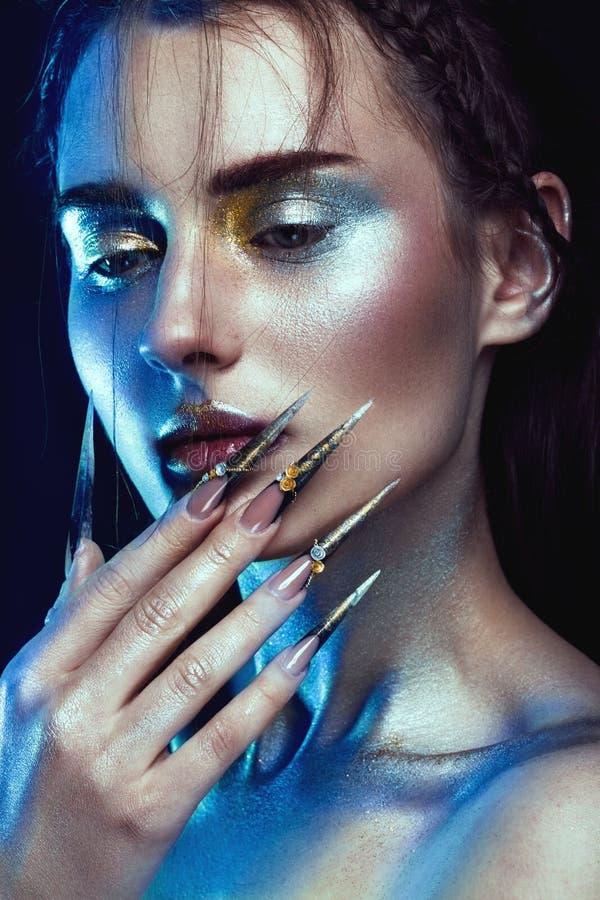 有创造性的金黄和银色闪烁构成的,长的钉子艺术美丽的女孩 秀丽表面 免版税图库摄影