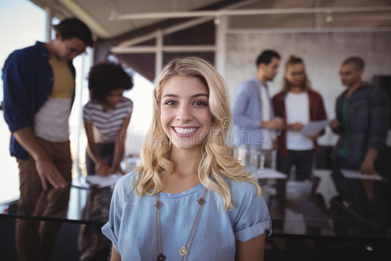 有创造性的队的微笑的女商人在背景中 库存图片