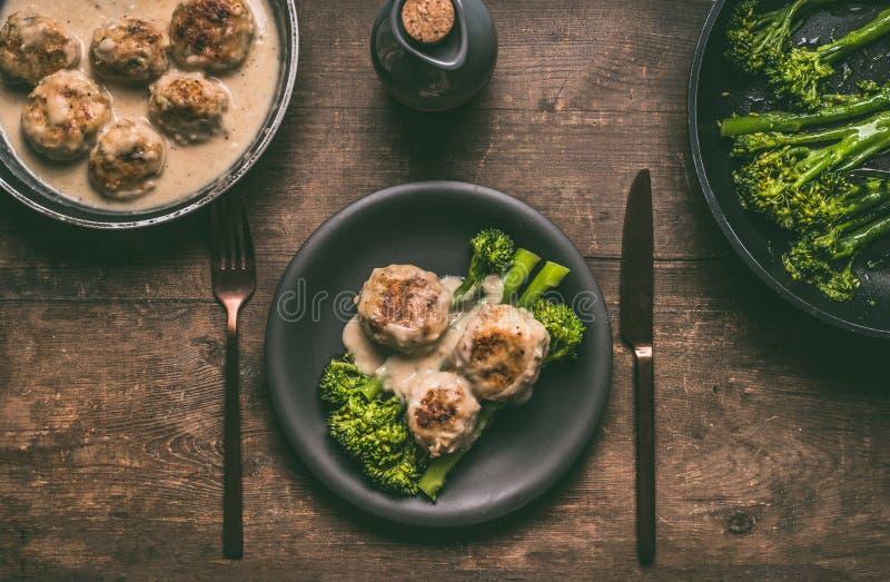 有利器和低碳节食的膳食的板材:肉丸和变白的硬花甘蓝在木桌背景 免版税库存图片