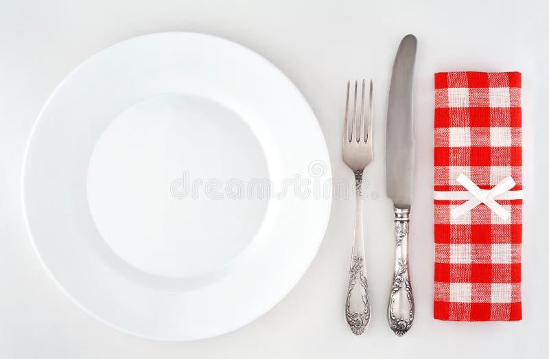 有利器和红色方格的餐巾的空的板材 免版税库存照片